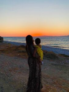 Woman holding child, pointing and looking out towards sea