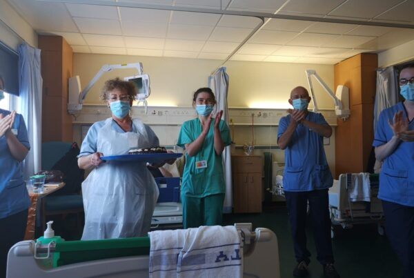 NHS staff with masks clapping and standing in hospital