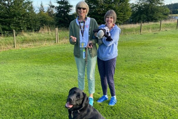 A photo of two women standing in a field and their black labrador sat in front of them