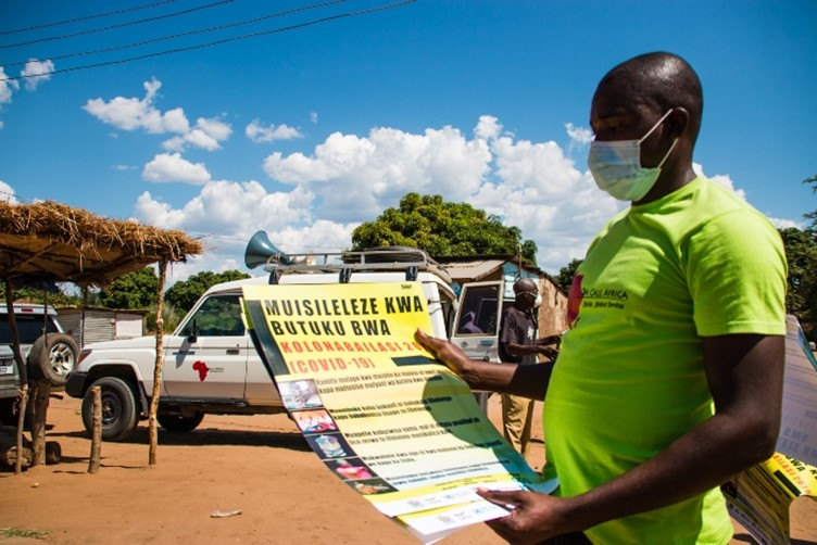 Man in yellow t-shirt with face mask reading a poster