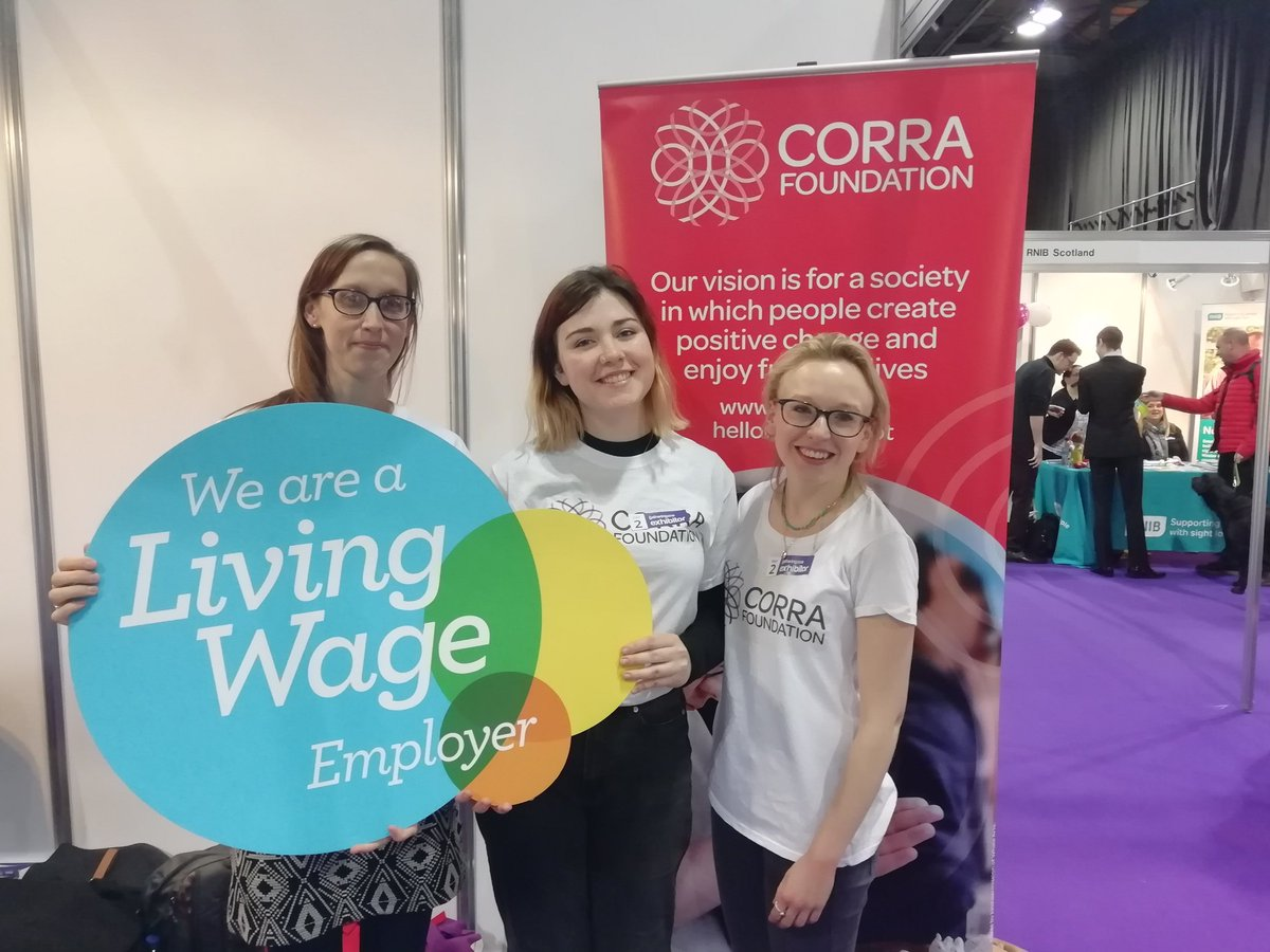 Corra staff holding living wage poster