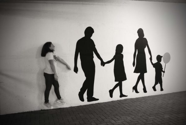 black and white image of girl next to wall art of family holding hands