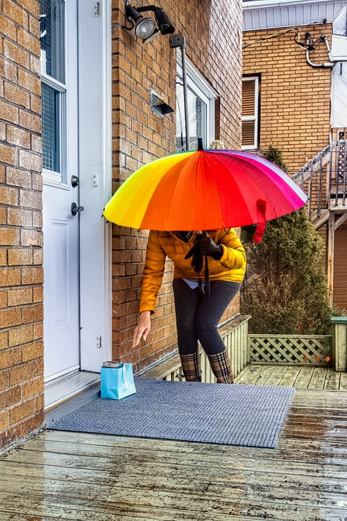 woman holding umbrella leaving a gift outside a front door