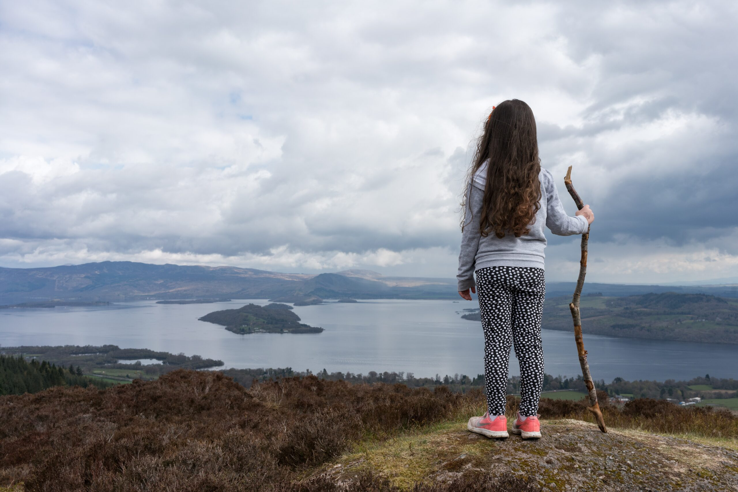 Girl with long brown hair stand on rock looking out onto hills holding a stick