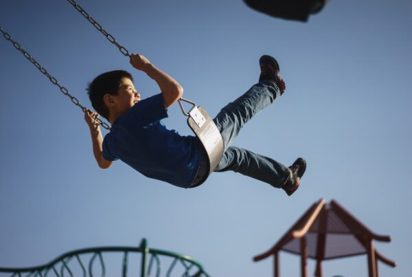 Boy smiling on swing in playground